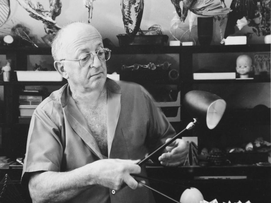 Serge Mouille dans son atelier manipulant une lampe Cocotte